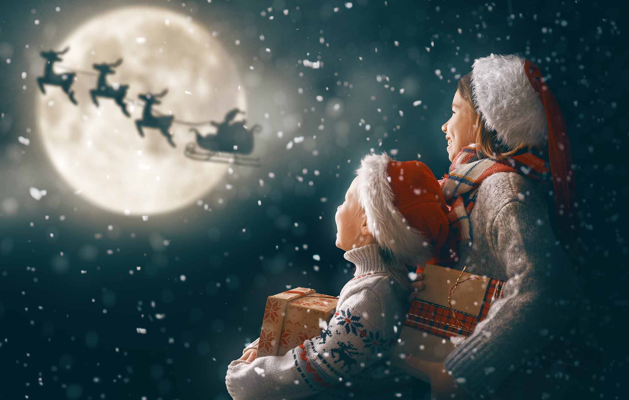 Merry Christmas and happy holidays! Cute little children with xmas presents. Santa Claus flying in his sleigh against moon sky. Kids enjoying the holiday with gifts on dark background.; Shutterstock ID 1558767518; Purchase Order: -